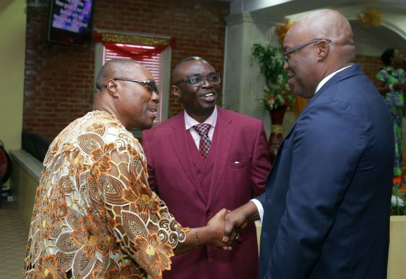 Bishop David Ibeleme, left, is introduced to THA Chief Secretary Kelvin Charles, right, by Bishop Ayotunde Akindele, pastor of the Victory Outreach Church.