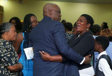 A church member greets THA Chief Secretary Kelvin Charles during the anniversary celebrations.