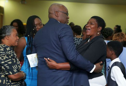 A church member greets THA Chief Secretary Kelvin Charles during the anniversary celebrations.