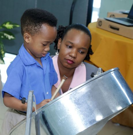 Young pannist Leston Paul of Hope Anglican Primary School plays as his mother Isabelle Burris-Paul watches and encourages him.