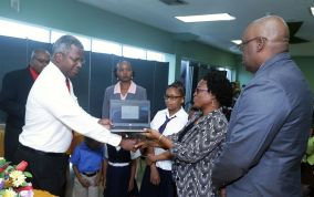 Dr Victor Wheeler presents Scarborough Methodist Primary School principal Diana Washington-Phillips with one of the Chromebook laptops as Chief Secretary Kelvin Charles, right, looks on.