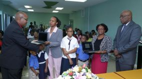 Leon Yearwood, brother of Dr Brian Yearwood, presents Hope Anglican Primary School teacher Isabelle Burris-Paul with a Chromebook laptop, as Chief Secretary Kelvin Charles, right, and pupils of the school and Scarborough Methodist Primary School principal Diana Washington-Phillips look on.