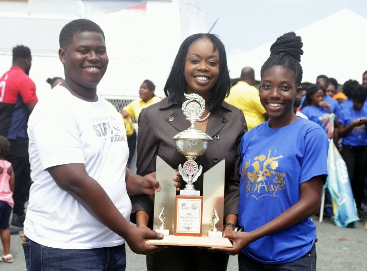 Kymani Sandy of Plymouth/Bethesda Pan Sensation and Aliyah Brooks of Speyside High School receive the trophy from Secretary of Tourism, Culture and Transportation Councillor Nadine Stewart-Phillips as joint winners in the under 21 category.