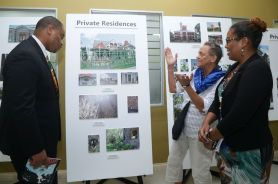 Secretary of Infrastructure, Quarries and the Environment Kwesi Des Vignes, left, looks on as amateur photographer Margaret Hinkson explains how she photographed sites in Tobago which now form part of the National Trust's photographic exhibition at the Scarborough Library Facility. With them is Heritage Preservation Officer Kara Roopsingh.