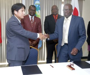 Japanese Counsellor and Deputy Head of Mission Yoshinori Yakabe, left, and Chief Administrator of the THA Raye Sandy, congratulate each other after signing an agreement for grant assistance for the CERT project run by TEMA. Looking on behind them are Chief Secretary Kelvin Charles, right, and Director of TEMA Allan Stewart.