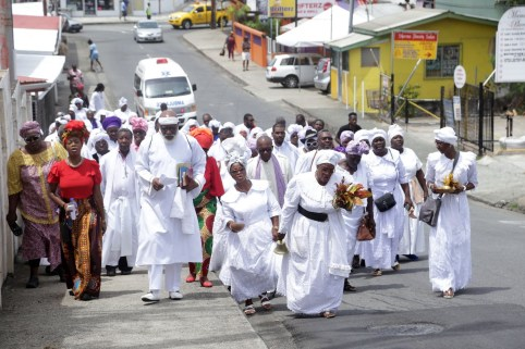 Secretary of Tourism, Culture and Transportation Nadine Stewart-Phillips (left) processes through Scarborough with members of the Spiritual Baptist community.