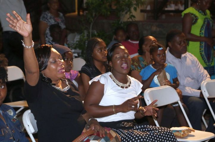 Two ladies close their eyes in worship as they sit in the audience.