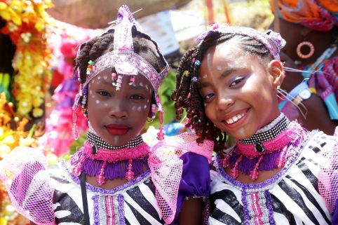 These two girls pose for a quick photo before the pre-race parade by masqueraders and cultural groups.