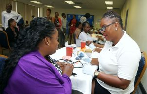 School health screening assistant Nicholette Williams, right, performs a blood pressure test on an employee of the Division of Finance and the Economy.