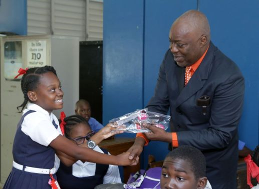 Black Rock Government Primary School student Giana Eastman is all smiles as she receives her SEA package containing stationery from Chief Secretary Kelvin Charles during his visit.