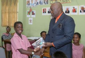 Jace Quashie, left, receives his SEA package from Chief Secretary Kelvin Charles during his visit to the St Nicholas Government Primary School.