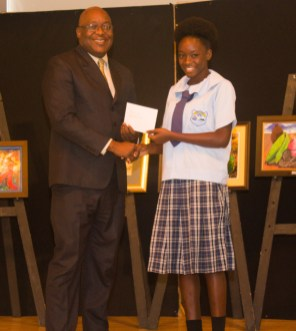 Chief Secretary Kelvin Charles presents a special award to Shayana Daniel of Speyside High School.