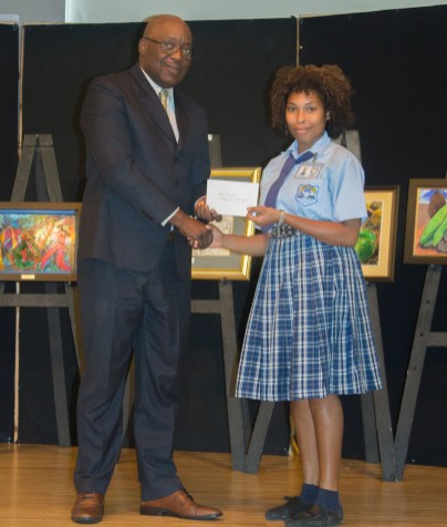 Kelly Theodore of Speyside High School receives her prize from Chief Secretary Kelvin Charles.