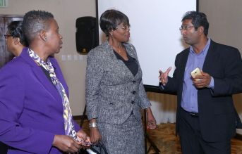 UWI Economist Dr Roger Hosein, right, chats with Secretary of Health, Wellness and Family Development Dr. Agatha Carrington, centre, and the Division's Administrator, Dianne Baker-Henry.
