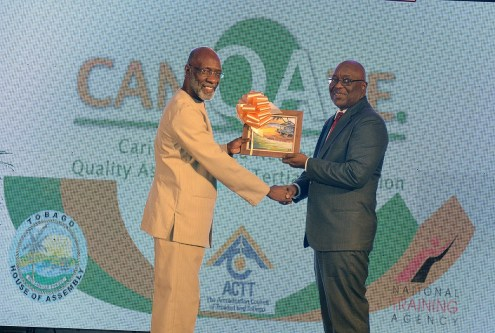 CANQATE President Vincent Alexander receives a token from Chief Scretary Kelvin Charles at the event.