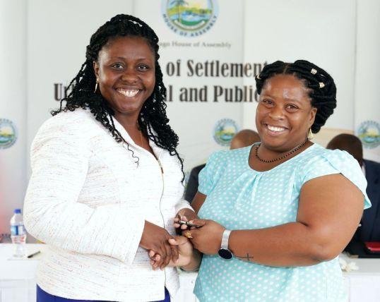 Area representative, Assemblyman Marisha Osmond, left, presents keys to townhouse recipient Renee Sampson.