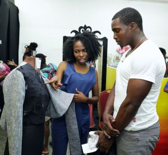 Student designer Antholyn Williams informs a visitor to the exhibition of her creative work.