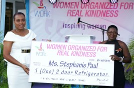 Stephanie Paul is gifted with a refrigerator from Shelly-Anne Baptiste during the event.