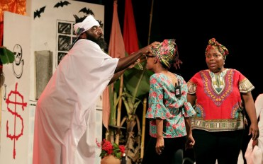 Leader Cyril (Anton Roberts) begins the process of exorcising spirits from Doodoo as Netta looks on.