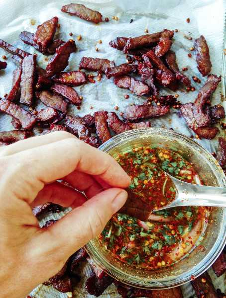 Homemade Thai Beef Jerky-Thai-Foodie: LOVE how Thai beef jerky is chewy and crispy and pairs perfectly with an easy Thai chili dipping sauce full of flavors like lime, shallots, cilantro, roasted rice powder and spicy Thai chili flakes! | thai-foodie.com