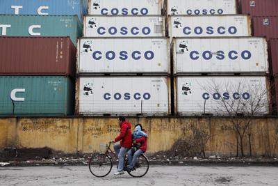 man rides his bicycle past stacked shipping containers carrying his wife and child in Shanghai, China on 09 January, 2009.