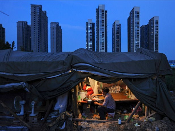 A labourer has his dinner under his shed at a construction site of a residential complex in Hefei, Anhui province, August 1, 2012. (Stringer/Courtesy Reuters)