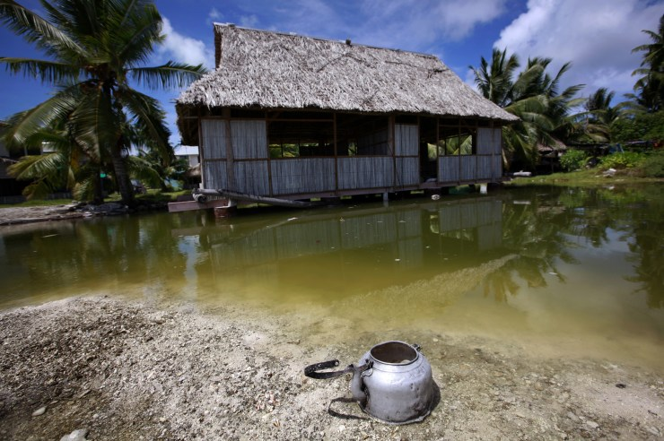An abandoned house that is affected by seawater during high-tides stands next to a small lagoon near the village of Tangintebu on South Tarawa in the central Pacific island nation of Kiribati May 25, 2013. Kiribati consists of a chain of 33 atolls and islands that stand just metres above sea level, spread over a huge expanse of otherwise empty ocean. With surrounding sea levels rising, Kiribati President Anote Tong has predicted his country will likely become uninhabitable in 30-60 years because of inundation and contamination of its freshwater supplies.