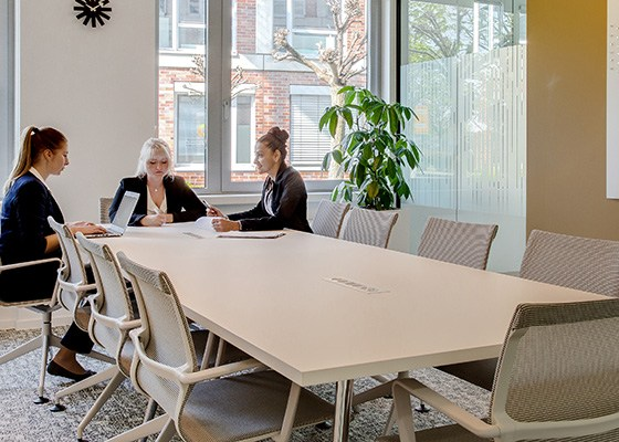 Three businesswomen sat around a large meeting table