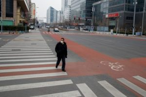 A man wears a face mask as he crosses a street in the Central Business District in Beijing as the country is hit by an outbreak of the novel coronavirus, China 24 February 2020. (Photo: Reuters/Thomas Peter).
