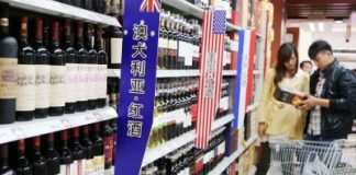 Chinese customers shop for wine imported from Australia, the United States or France at a supermarket in Xuchang city, central China