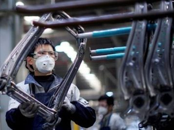 An employee wearing a face mask works on a car seat assembly line at Yanfeng Adient factory in Shanghai, China, as the country is hit by an outbreak of the new coronavirus disease (COVID-19), 24 February 2020 (Photo: Reuters/Aly Song).
