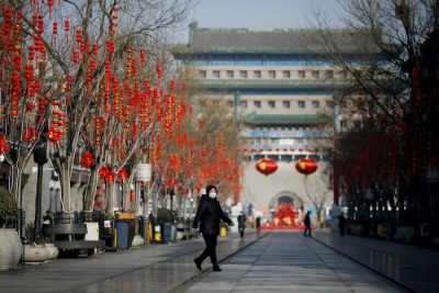 A woman wearing a face mask walks on the Qianmen pedestrian street in the morning after the extended Lunar New Year holiday caused by the novel coronavirus outbreak, in Beijing, China 10 February, 2020 (Photo: Reuters/Carlos Garcia Rawlins).