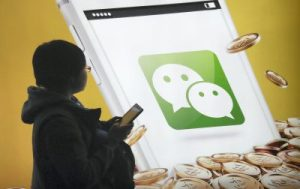 A pedestrian looks at an advertisement for the mobile messaging app Weixin, or WeChat, of Tencent in Beijing, China, 16 February 2015 (Photo: Reuters/Wu Changqing).