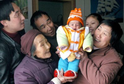 Parents, grandparents and a great grandmother hold up a baby at a home in Yangguidian village, Hubei province, 9 February 2005 (Photo: Reuters).