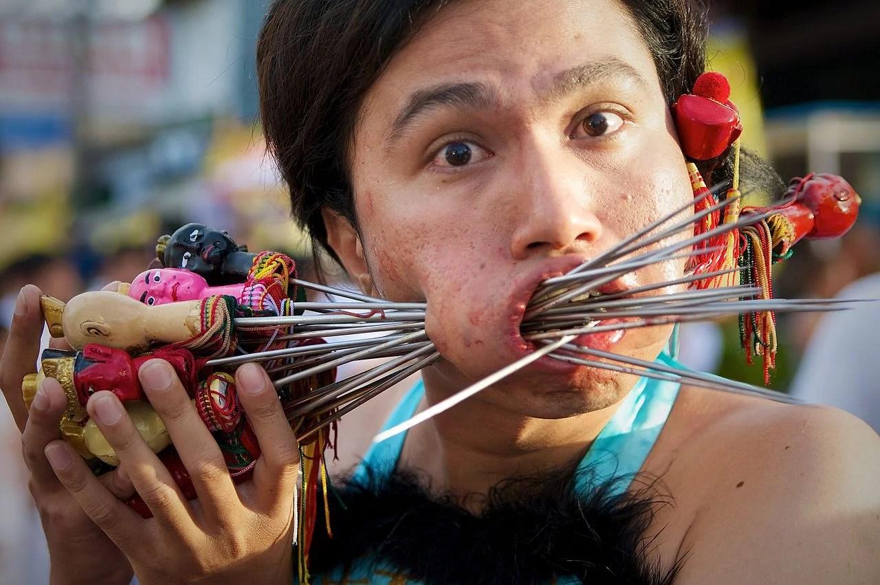 homme se transperçant les joues au festival végétarien phuket