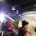 Thai police using water cannon to disperse protesters on Rama I Road in Bangkok, beneath Siam BTS Station, on 16 October 2020