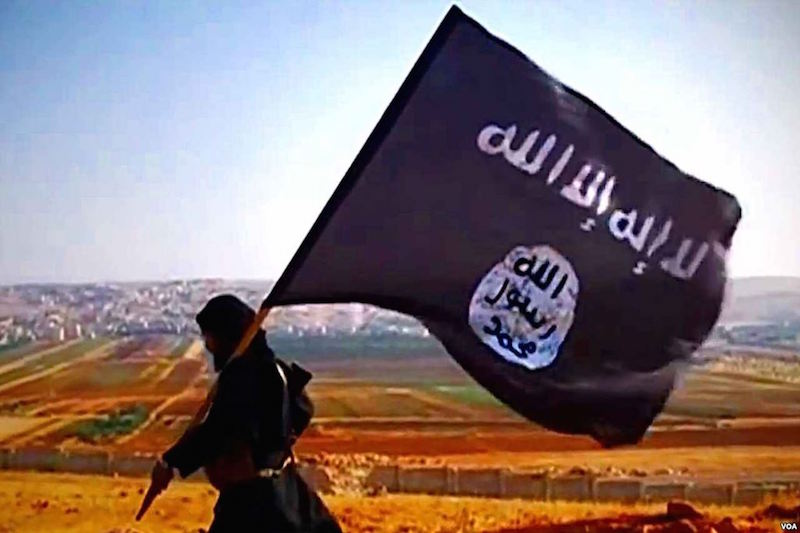 Daesh militant waving a ISIS flag