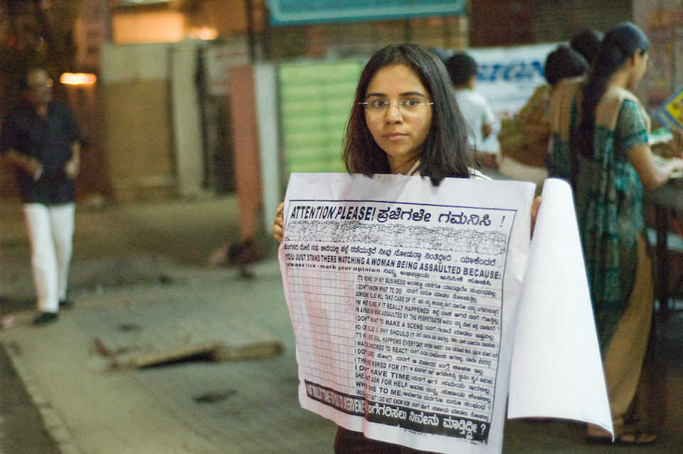 Indian girl at Church Street in Bangalore holding a sign to spread awareness about rape