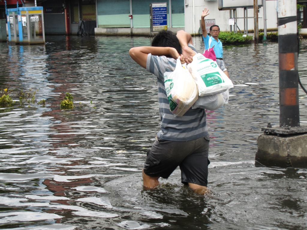 Man carrying bags during Thailand floods in November 2011