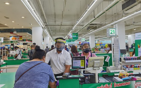 Supermarket cashiers wear masks and face shields to maintain physical distance amid the COVID-19 outbreak in Bangkok