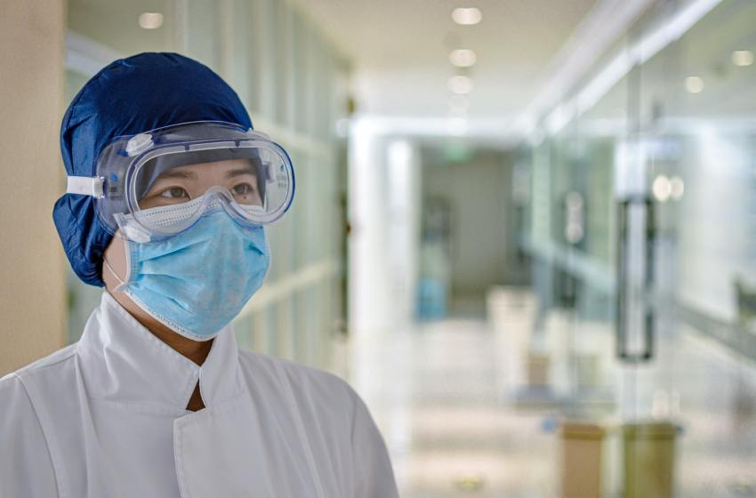 Medical staff wearing a blue face mask and glasses