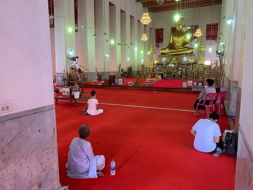 Buddhists keeping physical distance during COVID-19 at Wat Mahathat Yuwarat Rangsarit, Bangkok on the Buddhist Atthami Bucha day