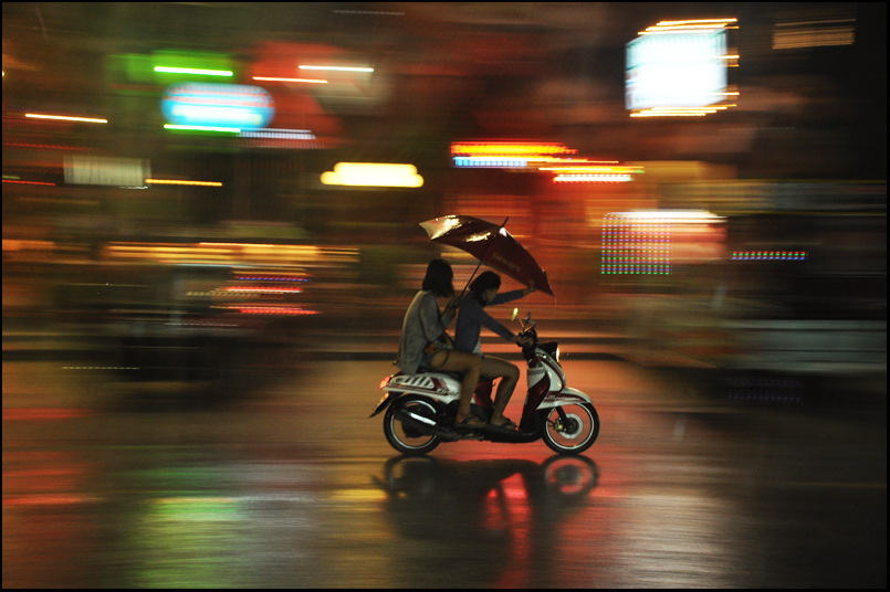 Couple with an umbrella riding a motorcycle in the rain