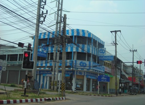 Street with low-hanging power line cables and buildings in Sakon Nakhon