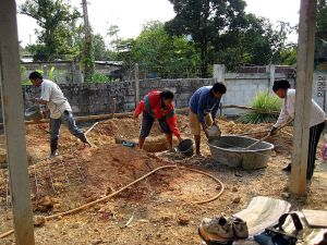 Workers mixing concrete in a tub and pouring it with buckets in Trat Province