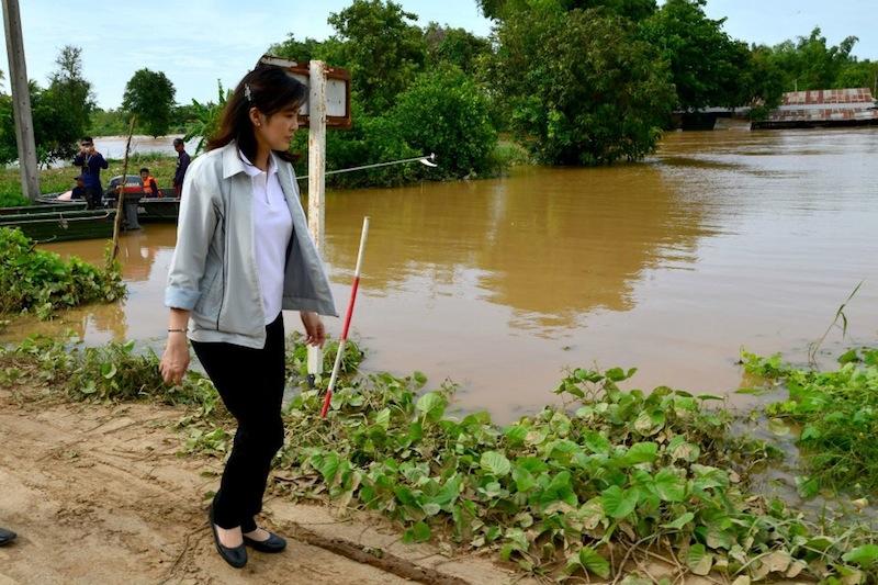 Yingluck Shinawatra walking near a pond