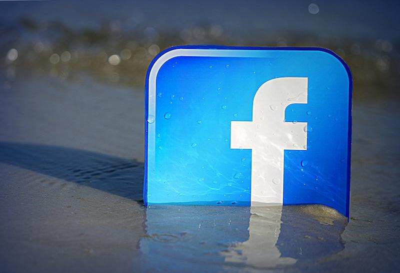Facebook logo semi buried in beach sand