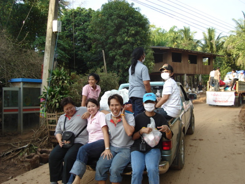 People sitting down on the back of a pick up in Laplae