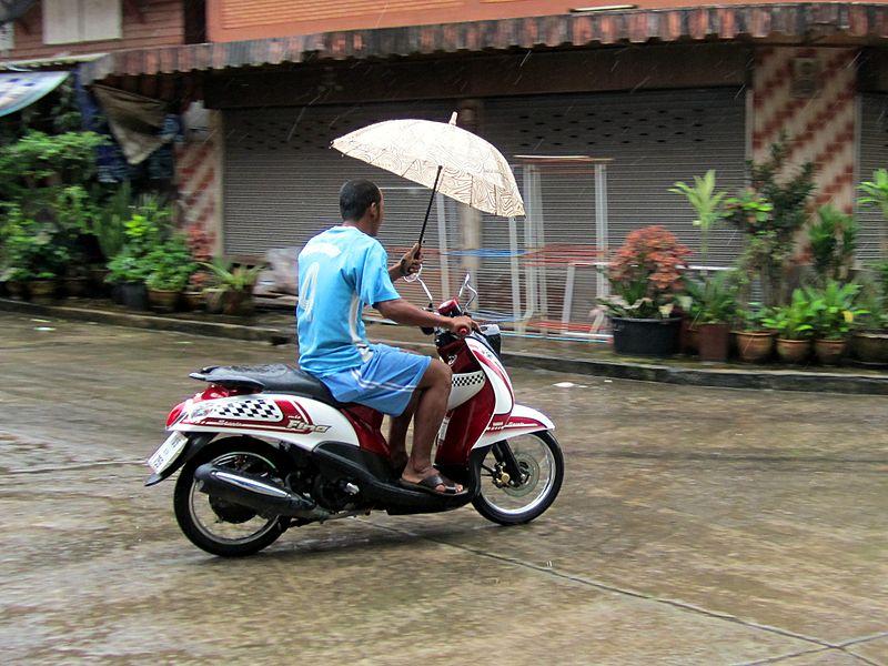 Thai man riding a Yamaha Mio Fino Sport scooter and holding an umbrella