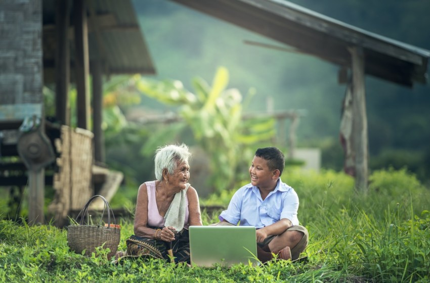 Thai grandmother and grandson using a laptop outdoors